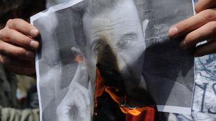 Un portrait du président syrien Bachar al-Assad brûlée lors d'une manifestation en Syrie (AFP/Bulent Kilic)