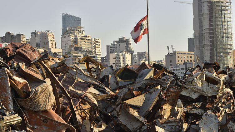 Un drapeau libanais trône, le 3 août 2021, au dessus du port dévasté de Beyrouth où un an plus tôt,des centaines de tonnes de nitrate d'ammonium, stockées depuis des années dans un entrepôt délabré, ont explosé. (HUSSAM SHBARO / ANADOLU AGENCY / AFP)