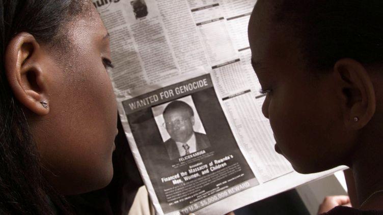 Des lecteurs d'un journal regardent un avis de recherche de Félicien Kabuga, le 12 juin 2002, à Nairobi (Kenya). (GEORGE MULALA / REUTERS)