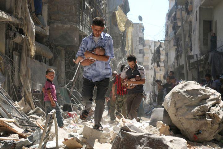 Pères syriens transportant leurs enfants dans les ruines d'Alep  (Ameer Alhalbi/ AFP)