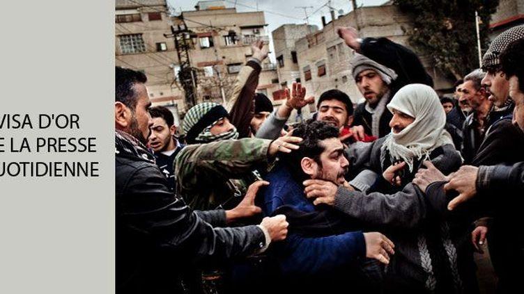 Le 27 janvier 2012, des manifestants frappent l'un des deux officiers de sécurité syriens (en bleu, au centre), infiltrés dans une cérémonie funéraire pour un combattant de l'Armée syrienne libre.  Ce combattant a été tué lors d'un échange de coups de feu avec les services de sécurité de Bachar el-Assad.  Voir le reportage (Tomas Munita / The New York Times)