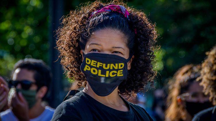 """Une manifestante réclame le """"définancement de la police"""", le 7 juin 2020, lors d'un rassemblement dans un parc de Brooklyn, à New York. (ERIK MCGREGOR/SIPA USA/SIPA)"""