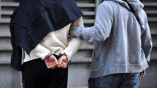 Un policier accompagne un suspect devant un juge d'instruction, le 14 octobre 2012, au palais de justice de Marseille (Bouches-du-Rhône). (GERARD JULIEN / AFP)