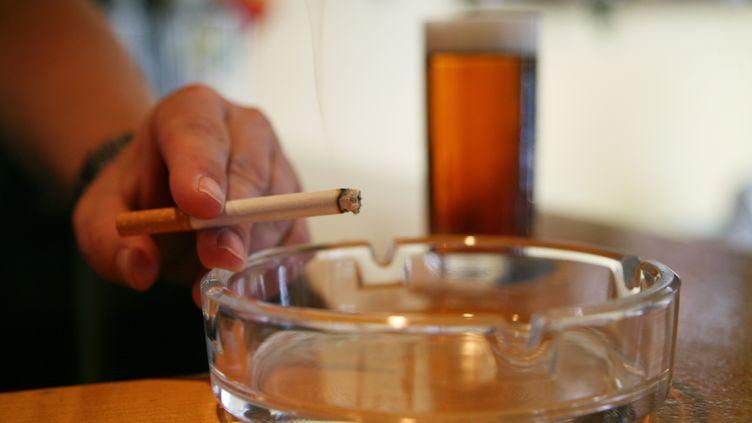 Illustration d'un hommetenant une cigarette, le 6 juillet 2010. (PATRIK STOLLARZ / AFP)