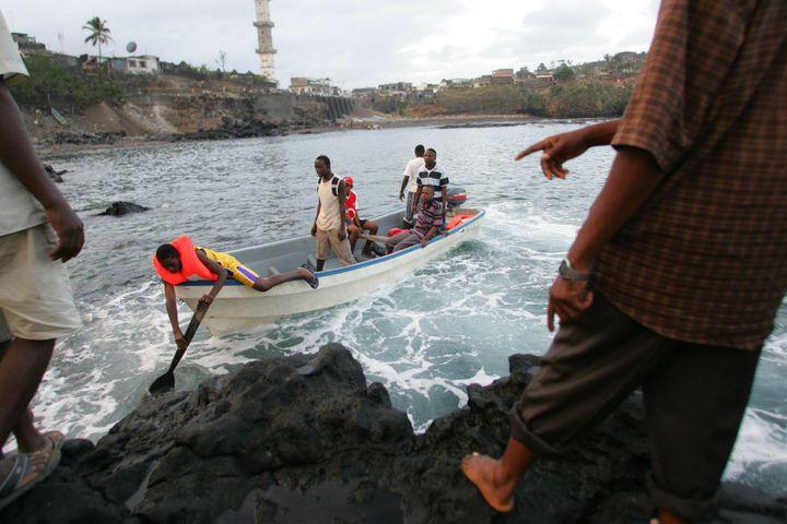Des clandestins en provenance de l'île d'Anjouan accostent sur l'île de Mayotte. Ces traversées dangereuses à bord de pirogues à moteur ont fait de nombreuses victimes. (Photo AFP/Richard Bouhet)