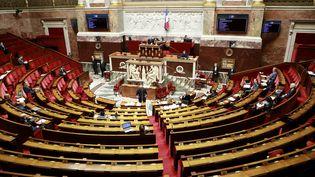 En effectfs réduits en raison de l'épidémie, les députés examinent le projet de loi d'urgence contre le Covid-19, le 21 mars 2020, à l'Assemblée nationale, à Paris. (LUDOVIC MARIN / AFP)