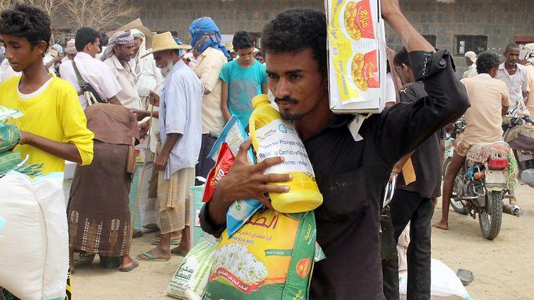 Des Yéménites, déplacés à cause du conflit, reçoivent une aide alimentaire de la part d'une ONG japonaise, à Abs, le 15 août 2018. (ESSA AHMED / AFP)