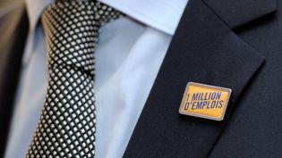 """Un membre du Medef arbore un pin's """"1 million d'emplois"""", lors d'une conférence de presse de l'organisation patronale à Marcq-en-Baroeul (Nord), le 13 janvier 2014. (PHILIPPE HUGUEN / AFP)"""