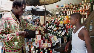 Un homme achète de l'alcool sur un marché d'Abidjan (Côte-d'Ivoire), le 29 avril 2001. (ISSOUF SANOGO / AFP)
