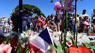 Des personnes se recueillent près de la promenade des Anglais, à Nice, le 15 juillet 2016. (GIUSEPPE CACACE / AFP)