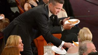Brad Pitt donne une part de pizza à Meryl Streep lors de la 86e cérémonie des Oscars, à Hollywood (Etats-Unis), le 2 mars 2014. ( JOHN SHEARER / AP / SIPA)