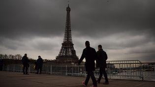 Des badauds marchent sur un pont près de la tour Eiffel, à Paris, le 6 janvier 2018, sous un ciel menaçant. (CHRISTOPHE SIMON / AFP)