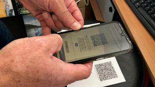 Un homme scan le QR code du pass sanitaire. (LISE ROOS WEIL / FRANCE-BLEU SUD LORRAINE)