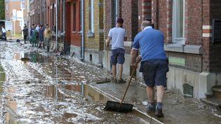 Des personnes nettoientla chaussée devant leur domicile, à Namur (Belgique), au lendemain de violentes pluies, le 25 juillet 2021. (NICOLAS MAETERLINCK / BELGA / AFP)