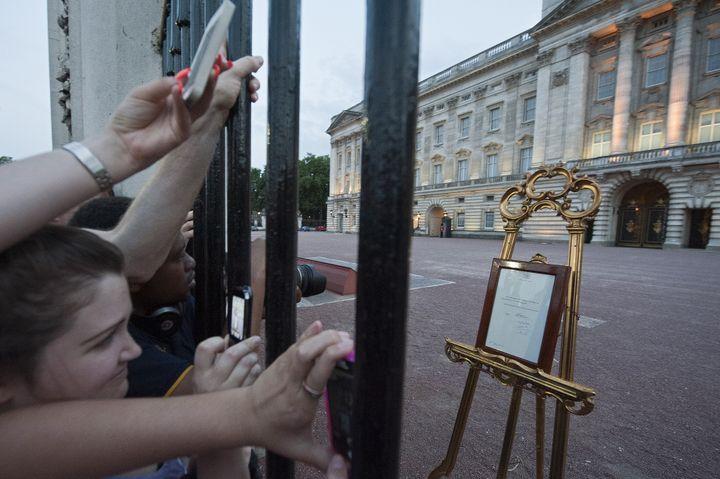 La foule se presse devant les grilles de Buckingham Palace pour lire l'annonce de la naissance du prince George, le 22 juillet 2013, à Londres. (WILL OLIVER / AFP)