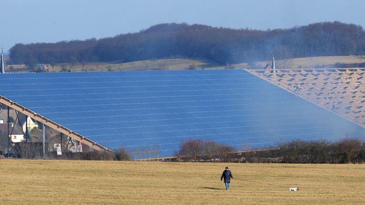 Une personne passe, le 18 février 2008 à Weinbourg (Bas-Rhin), devant les panneaux d'un parc photovoltaïque. (FREDERICK FLORIN / AFP)