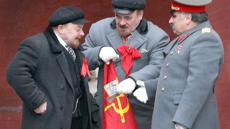 Deux sosies de Lénine et un sosie de Staline autour d'un drapeau soviétique, le 7 janvier 2009, sur la place Rouge, à Moscou, en Russie. (ALEXEY SAZONOV / AFP)