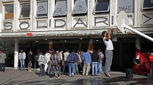 Des migrants dans la cour du lycée désaffecté Jean-Quarré, le 6 octobre 2015 à Paris. (FLORIAN DAVID / AFP)