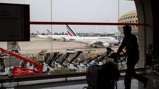 Un passager transporte ses bagages au sein de l'aéroport de Roissy (Val-d'Oise), le 24 septembre 2014. (  MAXPPP)