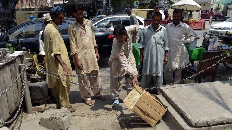 A Lahore, des Pakistanais observent l'endroitoù une femme enceinte a été tuée par lapidation. (ARIF ALI / AFP)