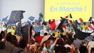 Des militants La République en Marche (LREM) agitent des drapeaux lors d'un meeting du parti, le 8 juillet 2017. (FRANCOIS GUILLOT / AFP)