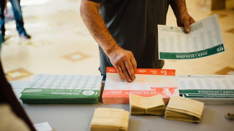 Un électeur prend des bulletins de vote pour les régionales et départementales, le 20 juin 2021, à Paris. (DELPHINE LEFEBVRE / HANS LUCAS / AFP)