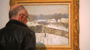 """Un homme regarde le tableau d'Alfred Sisley, """"Effet de neige à Louveciennes"""", en septembre 2011,aumusée Von der Heydt, à Wuppertal, en Allemagne. (PATRIK STOLLARZ / AFP)"""