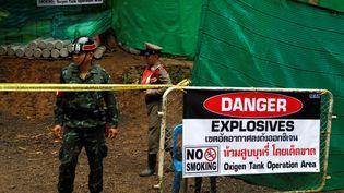Un policier se tient devant l'entrée de la grotte de Tham Luang (Thaïlande), où sont piégés douze adolescents accompagnés de leur entraîneur, le 8 juillet 2018. (SOE ZEYA TUN / Reuters)