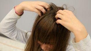 Une fille cherche des poux dans ses cheveux. (MAXPPP)