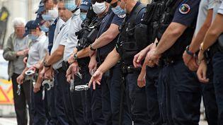 Des policiers jettent symboliquement leurs menottesle lundi 15 juin, devant le commissariat de police de Nancy, pour protester contre les déclarations du ministre de l'intèrieur (CEDRIC JACQUOT / MAXPPP)