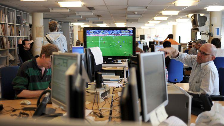 Un match de foot diffusé pendant les heures de travail au service des sports de l'AFP, à Paris. (FRED DUFOUR / AFP)