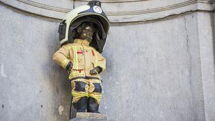 LeManneken Pis dans son costume de pompier destiné à rendre hommage aux secouristes intervenus lors des attentats de Bruxelles, le 22 mars 2017. (NICOLAS LAMBERT / BELGA MAG / AFP)