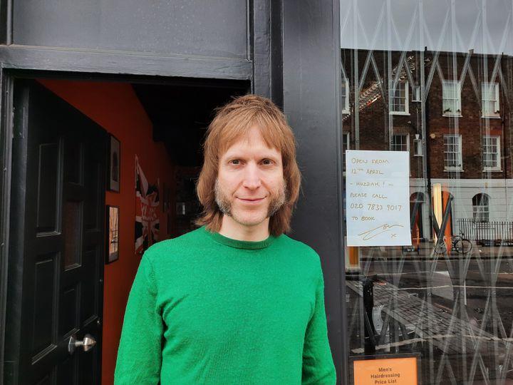 Tom devant son salon de coiffure, à Londres, le 25 février 2021. (RICHARD PLACE / RADIO FRANCE)