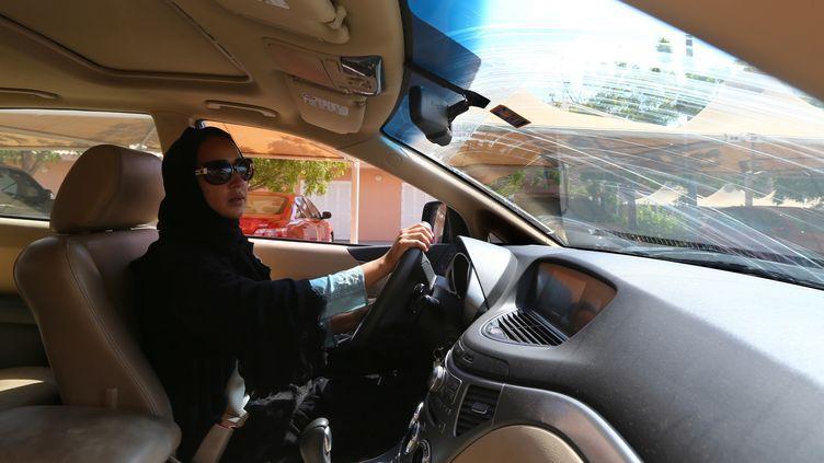 A partir du mois de juin 2018, les femmes auront le droit de conduire en Arabie Saoudite. Ici, l'activiste saoudienne Manal al Sharif conduit aux Emirats Arabes unis en 2013. (MARWAN NAAMANI / AFP)