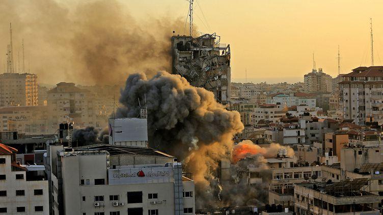 Une épaisse fumée se dégage d'un immeuble de Gaza en train de s'écrouler après une frappe de l'armée israélienne, le 12 mai 2021. (QUSAY DAWUD / AFP)