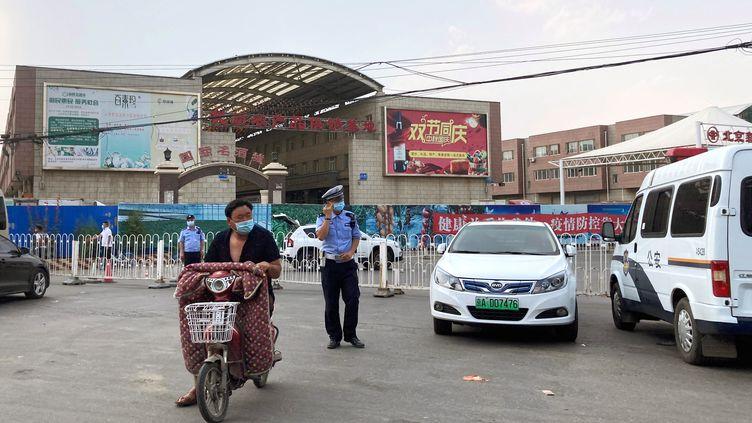 Des officiers de police montent la garde devant le marché de Xinfadi, fermé à cause d'une recrudescence de cas de Covid-19, le 13 juin 2020. (MARTIN POLLARD / REUTERS)