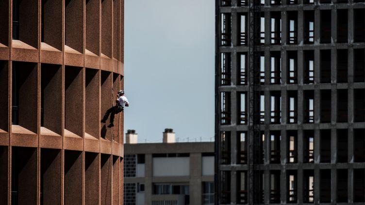 """Un soldat escalade la tour du """"Crayon"""", à Lyon, le 6 juin 2018. (JEFF PACHOUD / AFP)"""