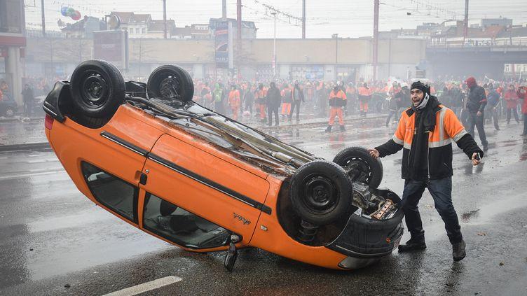 La photo de cette voiture, retournée et brûlée le 6 novembre 2014 à Bruxelles lors d'une manifestation anti-austérité, a fait le tour des médias belges. (LAURIE DIEFFEMBACQ / BELGA MAG / AFP)