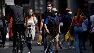 Des passants portant des masques marchent dans les rues. (JOHN THYS / AFP)