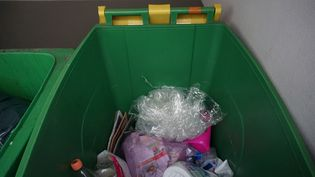 Dans un immeuble du 12e arrondissement de Paris, des sacs et emballages plastique remplissent le bac jaune censé partir pour le recyclage. (JULIE RASPLUS / FRANCETV INFO)