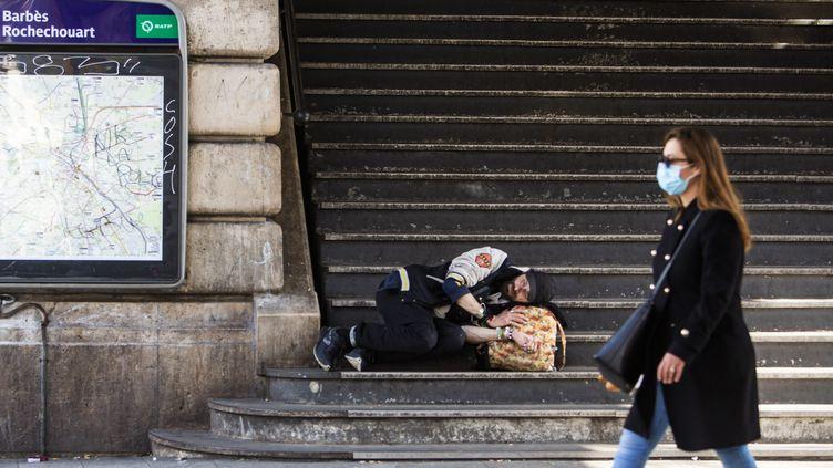 Une femme avec un masque passe devant un SDF à Paris, le 19 mars 2020. (ALEXIS SCIARD / MAXPPP)