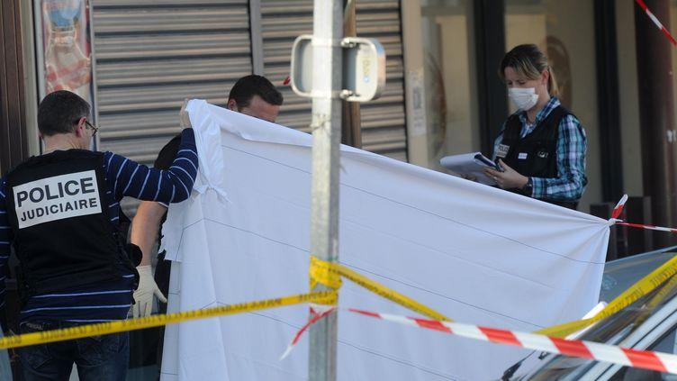 Des policiers inspectent les lieux après le meurtre en pleine rue de deux soldats, jeudi 15 mars à Montauban (Tarn-et-Garonne). (ERIC CABANIS / AFP)
