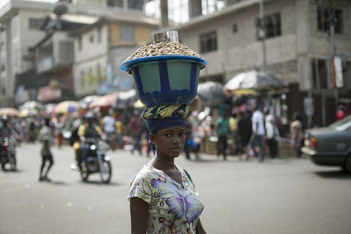 Une femme porte sur la tête un récipient rempli d'arachides à Freetown, capitale de la Sierra Leone, le 16 décembre 2014. (BAZ RATNER / X02483)