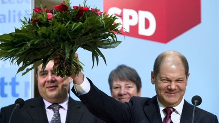 Le future maire SPD de Hambourg, Olaf Scholze (à droite), brandit les fleurs de la victoire. (AFP - JOHANNES EISELE)