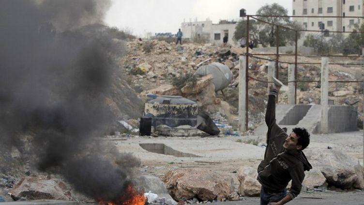Un Palestinien jette une pierre sur les forces israéliennes au checkpoint de Qalandia, dans la bande de Gaza, le 19 novembre 2012. (AHMAD GHARABLI / AFP)