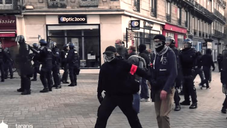 Deux policiers en civil portant un foulard à tête de mort s'avancent vers des manifestants, lors d'un rassemblement en hommage à Rémi Fraisse, à Nantes (Loire-Atlantique), le 1er novembre 2014. (TARANIS NEWS / FRANCETV INFO)