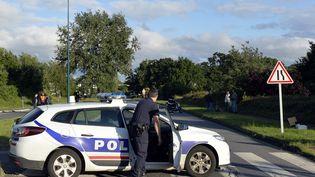 Un policier bloque une route avec sa voiture de patrouille, le 22 juin 2013, à Saint-Ouen-l'Aumône (Val-d'Oise) (photo d'illustration). (MIGUEL MEDINA / AFP)