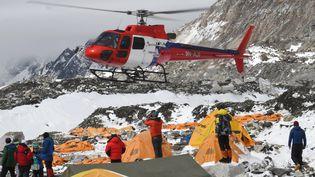 Un hélicoptère se pose au camp de base de l'Everest, touché par des avalanche, pour secourir les blessés, dimanche 26 avril 2015. (ROBERTO SCHMIDT / AFP)