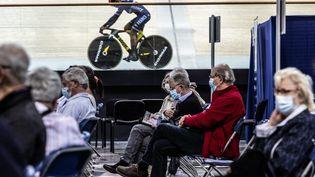 Un membre de l'équipe de France de cyclisme sur piste s'entraîne sous le regard des personnes qui viennent de se faire vacciner contre le Covid-19 dans le centre de vaccination du vélodrome de Saint-Quentin-en-Yvelines. (SADAK SOUICI / LE PICTORIUM / MAXPPP)