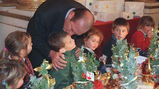 Jacques Chirac embrasse un enfant du personnel de la présidence de l'Elysée, le 17 décembre 1997. (PASCAL GUYOT / AFP POOL / AFP)